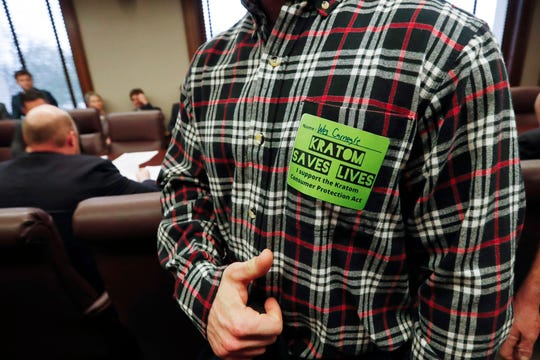 """An adult supporter of the herbal supplement kratom gives a """"thumbs up"""" at a Senate committee meeting at the Capitol in Jackson, Miss., Monday, March 2, 2020. Mississippi legislators have killed bills that would either ban or regulate kratom, an herbal drug that can be used for pain relief."""